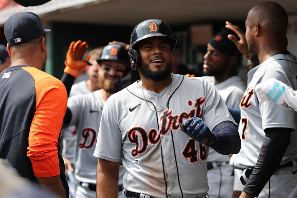 Detroit Tigers' Jeimer Candelario (46) smiles in the dugout after scoring on a sacrifice fly off the bat of Eric Haase, rear left, during the sixth inning of a baseball game against the Cincinnati Reds, Sunday, Sept. 5, 2021, in Cincinnati.