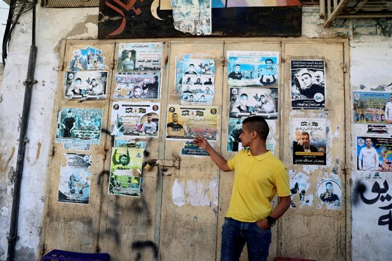 """Palestinian Ashraf Ahmed stands in front of a wall lined with posters of """"martyrs"""" of the two Palestinian uprisings (intifadas)"""