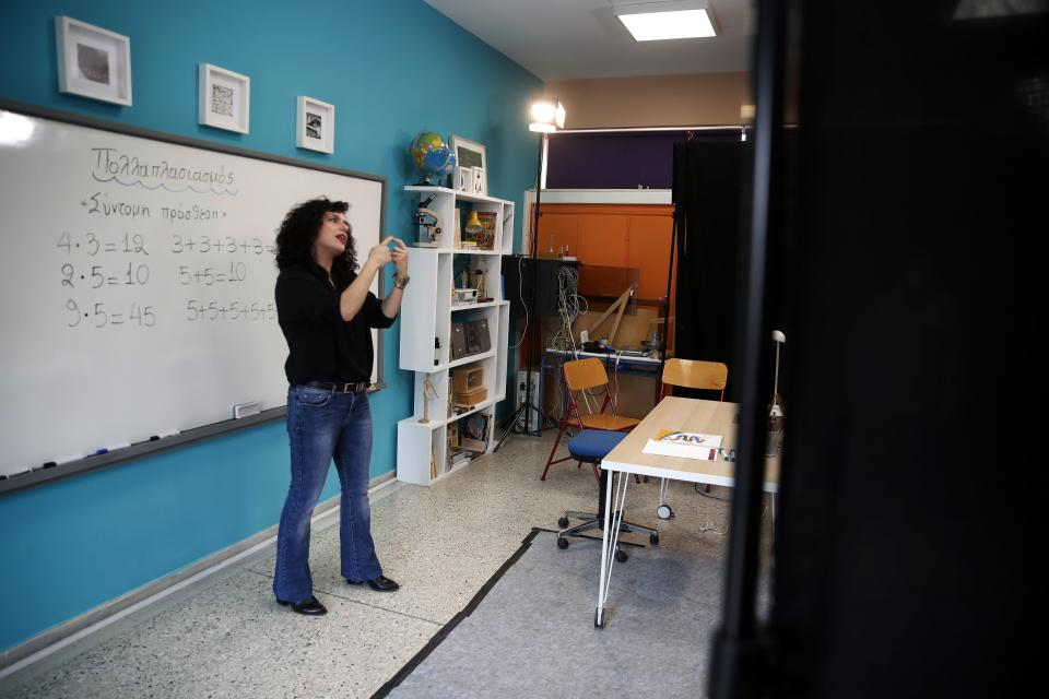 Teacher Rania Koukli records lessons that are broadcast on public television, at an elementary school in Athens, Wednesday, Nov. 18, 20202. Most other European countries have vowed to keep schools open, but the pandemic has hit Greece hard for the first time in recent weeks following a successful lockdown in the spring, overwhelming hospitals in parts of the country. State television is making and broadcasting lessons, while teachers sit in empty classrooms talking to remote students. Despite some problems, they say it keeps children in touch with their schools. (AP Photo/Thanassis Stavrakis)