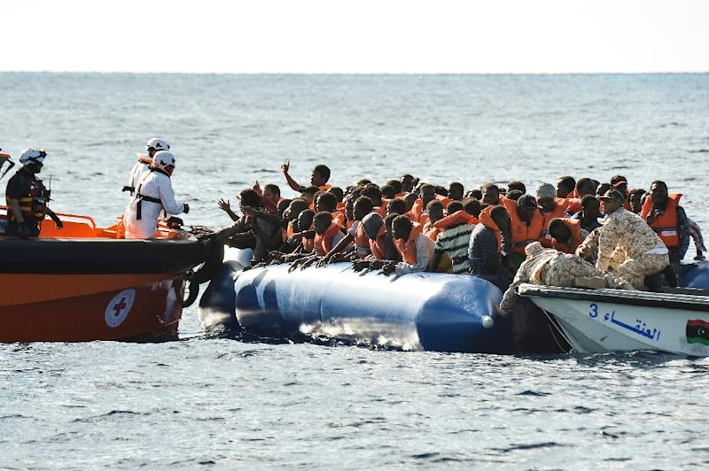 migrants and refugees sit on a rubber boat during a rescue operation