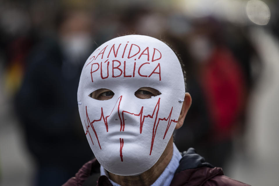 """A demonstrator attends a protest to demand more resources for public health system in Madrid, Spain, Sunday, Nov. 29, 2020. The organizers delivered a manifesto to the Madrid regional authorities demanding the end privatization of the health system. The mask reads in Spanish """"Public health system"""". (AP Photo/Bernat Armangue)"""