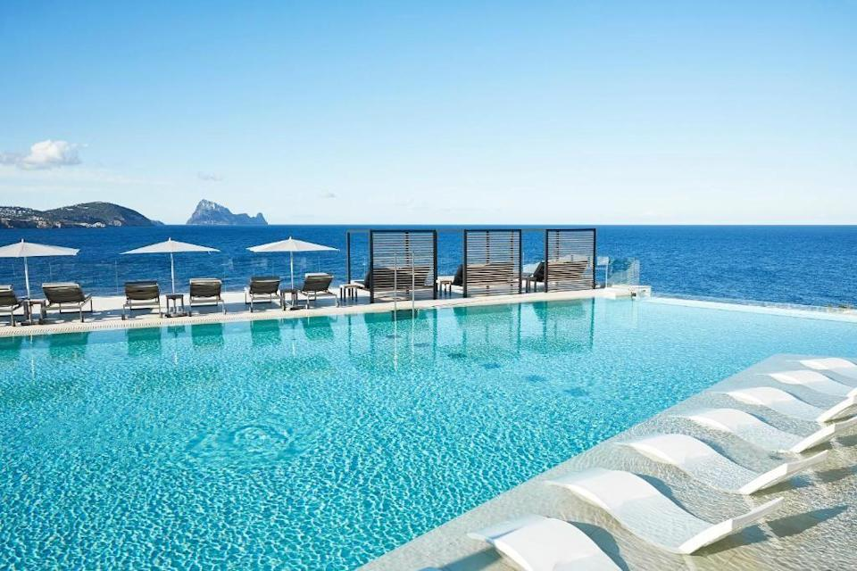 """<p>If it's all-out swank you're after, then look no further than the <a href=""""https://www.booking.com/hotel/es/seven-pines-resort-ibiza.en-gb.html?aid=2070929&label=ibiza-hotels"""" rel=""""nofollow noopener"""" target=""""_blank"""" data-ylk=""""slk:7 Pines"""" class=""""link rapid-noclick-resp"""">7 Pines</a> in Sant Josep de sa Talaia, or San Jose. Named after the sweet, sweet scent of Ibiza's native conifer forests, this beachfront resort has staggeringly pretty views over Es Vedrà rock. Widely regarded as one of the best hotels in Ibiza, the sprawling resort features whitewashed Cubist-style villas housing 186 split-level suites, every one with a private pool, plus two-bedroom pads which work well for families. </p><p>Relax in the Pure Seven spa, which has a thermal hydrotherapy circuit, or splash around in one of the two pools, our favourite is the infinity pool which overlooks Es Vedrà. There are several restaurants, including The View, a fine dining spot offering European dishes with a Korean twist, plus a clutch of bars, including the Pershing Yacht Terrace, which clasped to the rugged cliffside, offers the ultimate sundowner.</p><p><a class=""""link rapid-noclick-resp"""" href=""""https://www.booking.com/hotel/es/seven-pines-resort-ibiza.en-gb.html?aid=2070929&label=ibiza-hotels"""" rel=""""nofollow noopener"""" target=""""_blank"""" data-ylk=""""slk:CHECK AVAILABILITY"""">CHECK AVAILABILITY</a></p>"""