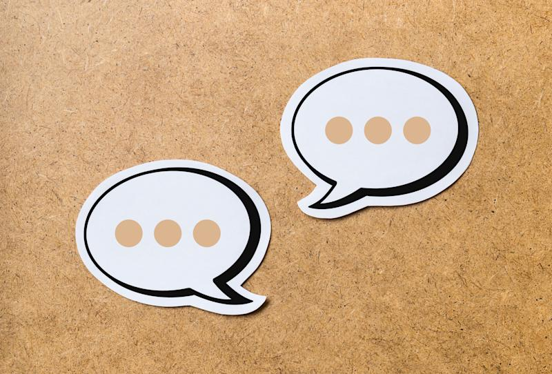 2 speech bubbles on a light brown wooden cork board background. Chat bubble and icon cut from paper and cardboard.