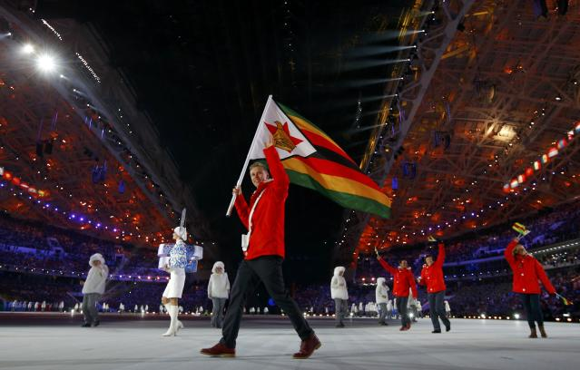 Zimbabwe's flag-bearer Luke Steyn waves as he leads his country's contingent during the opening ceremony of the 2014 Sochi Winter Olympic Games February 7, 2014. REUTERS/Brian Snyder (RUSSIA - Tags: SPORT OLYMPICS)