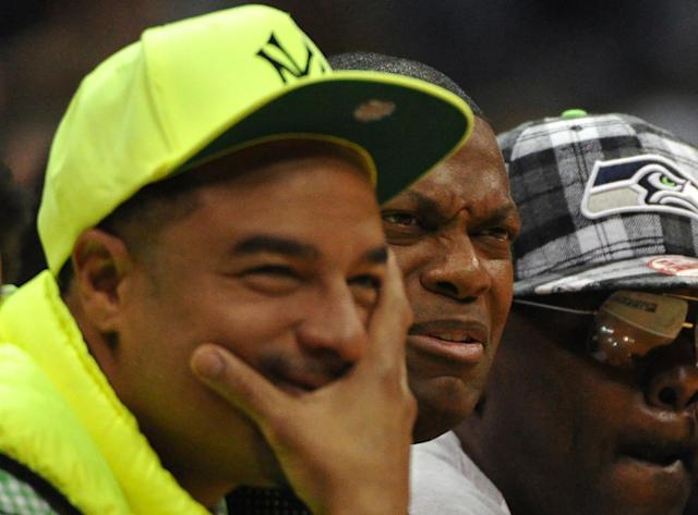 Actor Chris Tucker, center, makes a face as he watches the Atlanta Hawks play the Toronto Raptors in the first half of their NBA basketball game Tuesday, March 18, 2014, in Atlanta. (AP Photo/David Tulis)