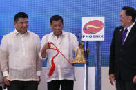 Philippine President Rodrigo Duterte, center, makes the ceremonial ringing of the bell during his visit for the first time at the Philippine Stocks Exchange to mark the 10th anniversary of the stock listing of Phoenix Petroleum at the financial district of Makati city, east of Manila, Philippines, Tuesday, July 11, 2017. Duterte said a disastrous siege by Islamic State group-aligned gunmen on a southern city of Marawi may end in 10 to 15 days but the threat posed by the brutal group will continue to plague the country. At left is Dennis Uy, CEO of Phoenix Petroleum, and at right is Jose Pardo, chairman of the Philippine Stocks Exchange. (AP Photo/Bullit Marquez)