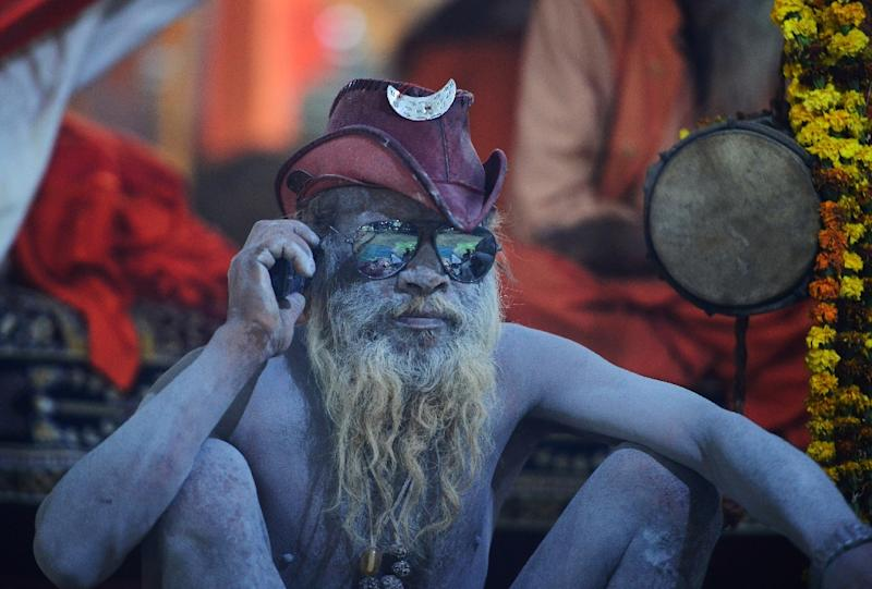Naked, dread-locked holy men smeared in ash and sadhus clad in saffron robes wander the crowds (AFP Photo/SANJAY KANOJIA)