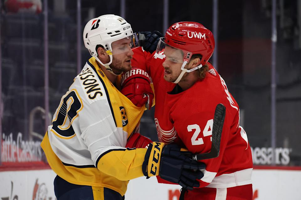 Jon Merrill (24) of the Detroit Red Wings mixes it up with Colton Sissons of the Nashville Predators during the first period  at Little Caesars Arena on Feb. 23, 2021.