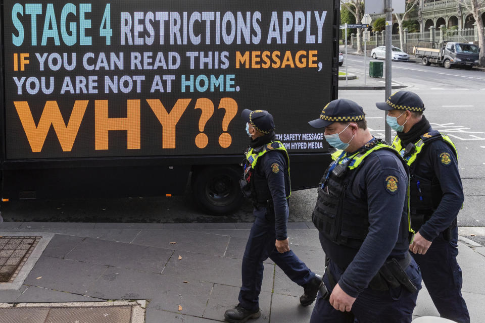 Victorian protective service officers are seen walking on patrol past a sign to urge people to stay home during lockdown. Source: AP