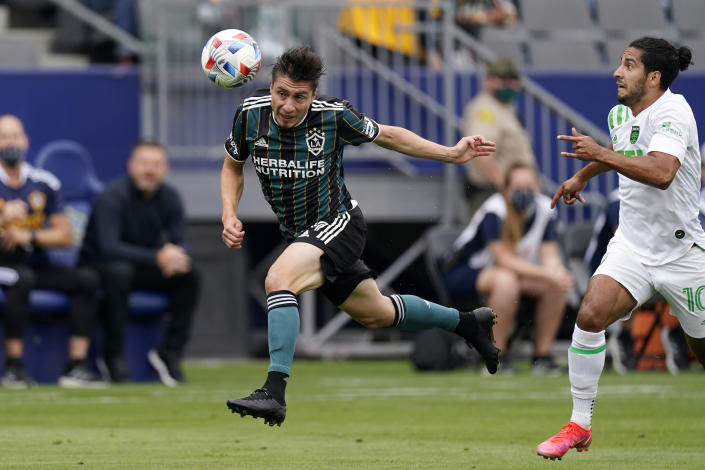 Los Angeles Galaxy defender Jorge Villafana, left, heads the ball as Austin FC forward Cecilio Dominguez chases him during the first half of a Major League Soccer match Saturday, May 15, 2021, in Carson, Calif. (AP Photo/Mark J. Terrill)