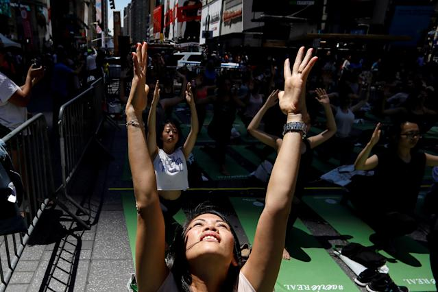 People participate in a yoga class during an annual Solstice event in the Times Square in New York City, U.S., June 21, 2018. REUTERS/Brendan McDermid TPX IMAGES OF THE DAY