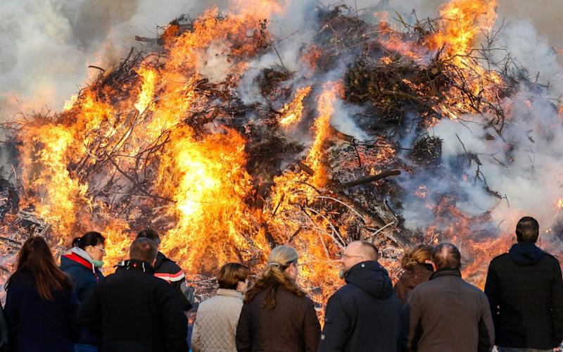 Spectators watch a traditional Easter fire in Uphusen near Bremen, northern Germany - Credit: Focke Strangmann/EPA