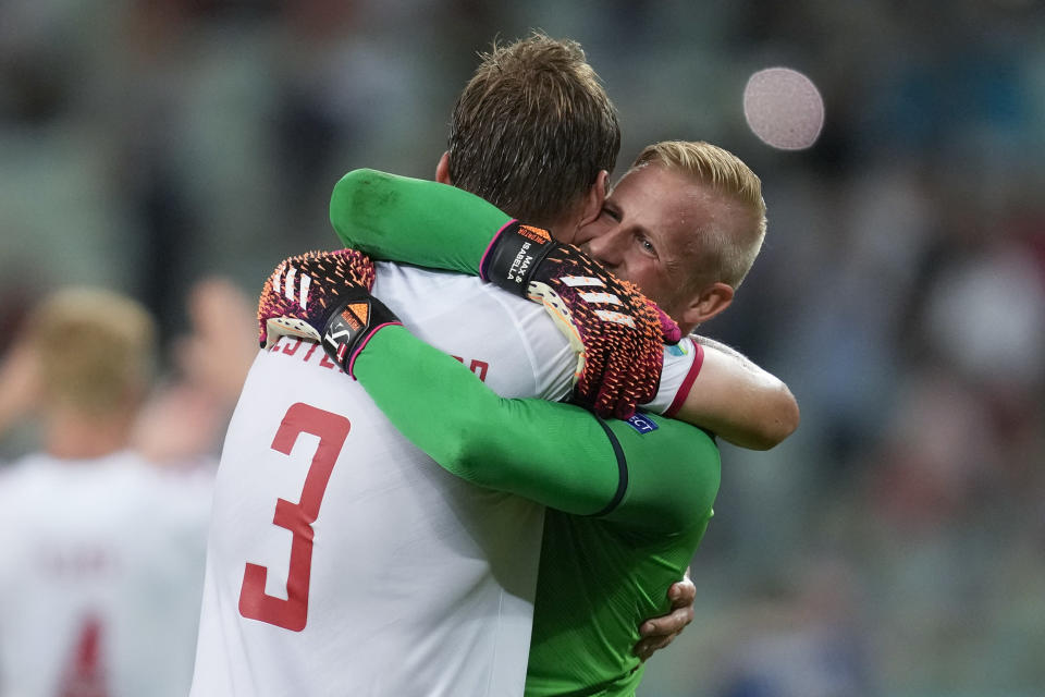 Denmark's goalkeeper Kasper Schmeichel, right, hugs Jannik Vestergaard at the end of the Euro 2020 soccer championship quarterfinal match between Czech Republic and Denmark, at the Olympic stadium in Baku, Saturday, July 3, 2021. Denmark won 2-1 and advances to the semifinals. (AP Photo/Darko Vojinovic, Pool)