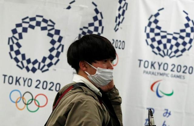 A man wearing a protective face mask, following an outbreak of the coronavirus disease (COVID-19), walks in front of flags of the Tokyo 2020 Olympic and Paralympic Games in Tokyo