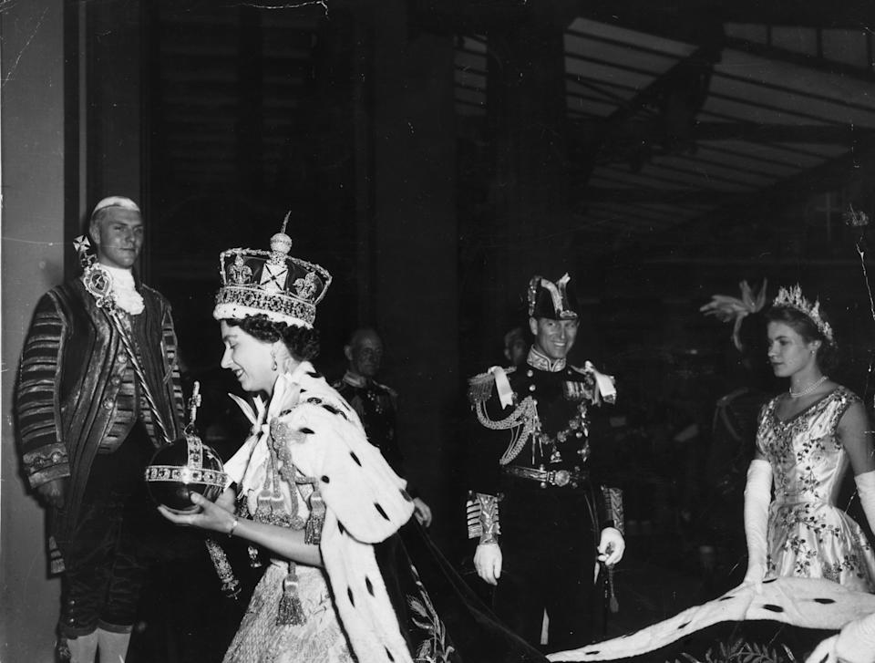 2nd June 1953:  Queen Elizabeth II, wearing the Imperial State crown and carrying the Orb and Sceptre, returns to Buckingham Palace from Westminster Abbey, London, following her Coronation.  (Photo by Topical Press Agency/Getty Images)