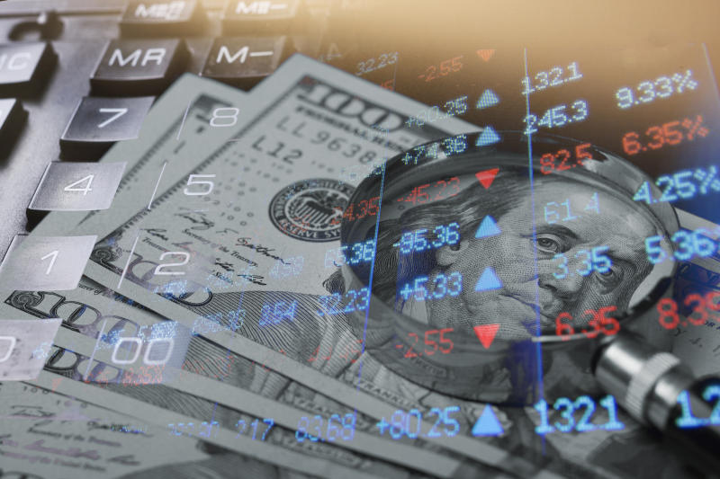 Stock index chart superimposed over hundred-dollar bills.