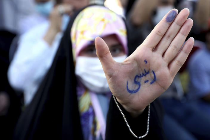 """A supporter of presidential candidate Ebrahim Raisi shows her hand with writing in Persian that reads """"Raisi"""", during a rally in Tehran, Iran, Wednesday, June 16, 2021. Iran's clerical vetting committee has allowed just seven candidates for the Friday, June 18, ballot, nixing prominent reformists and key allies of President Hassan Rouhani. The presumed front-runner has become Ebrahim Raisi, the country's hard-line judiciary chief who is closely aligned with Supreme Leader Ayatollah Ali Khamenei. (AP Photo/Ebrahim Noroozi)"""