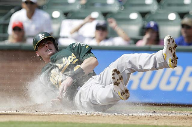 Oakland Athletics' Josh Donaldson (20) rolls over the plate after an awkward slide at home as he scored on a double by Brandon Moss in the first inning of a baseball game against the Texas Rangers, Saturday, Sept. 14, 2013, in Arlington, Texas. (AP Photo/Tony Gutierrez)