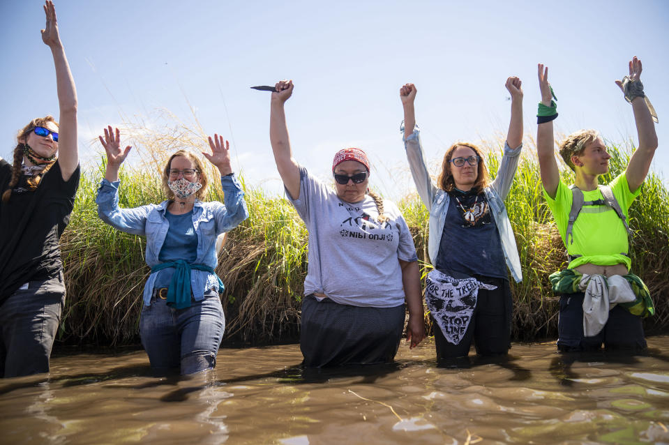 """Everlasting Wind, aka Dawn Goodwin, joins others by raising her fist in the Mississippi River near an Enbridge pipeline construction site, on Monday, June 7, 2021, in Clearwater County, Minn., to protest the construction of Enbridge Line 3. Goodwin is a co-founder of RISE Coalition. More than 2,000 Indigenous leaders and """"water protectors"""" gathered in Clearwater County from around the country. The day started with a prayer circle and moved on to a march to the Mississippi headwaters where the oil pipeline is proposed to be built. (Alex Kormann/Star Tribune via AP)"""