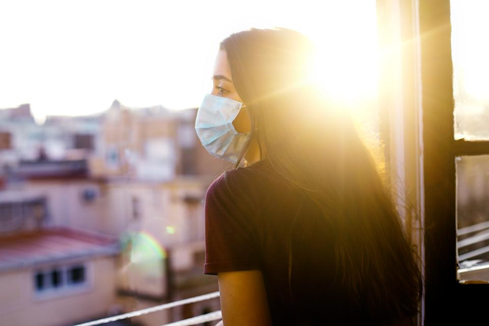 teenage girl wearing protective mask, looking at the city from the window during coronavirus qurantine in Barcelona. Nice sunset with the sun shining in the sky