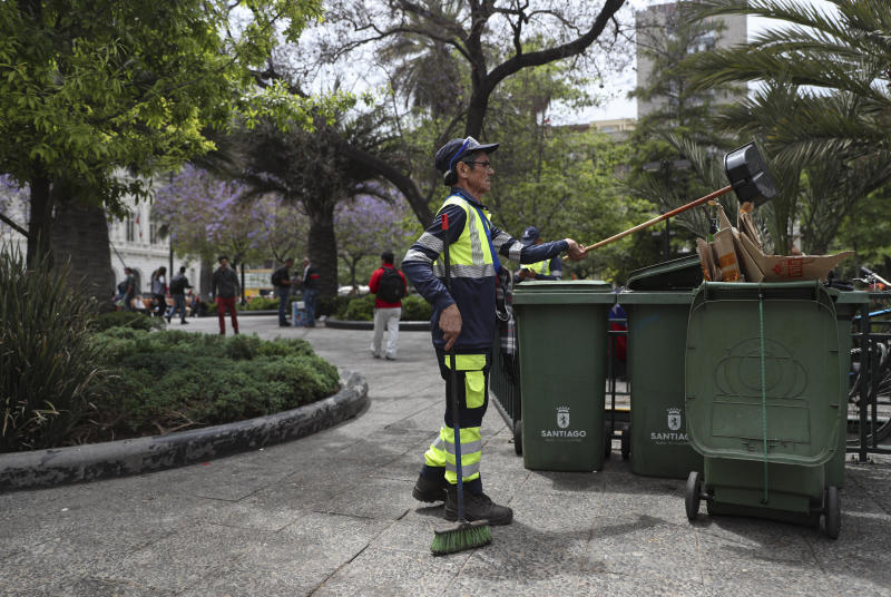 "In this Nov. 4, 2019 photo, retired Segundo Vergara, 69, works cleaning the Plaza de Armas in downtown Santiago, Chile.  Vergara, who earns 400,000 pesos ($530) a month as a cleaner, said while attending a demonstration in Santiago that if his wife wasn't working, ""we would be living off bread and water, eating rice and pasta every day.""  (AP Photo/Esteban Felix)"
