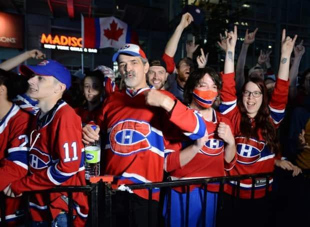 Montreal Canadiens fans react as they watch Game 5 Stanley Cup final action against the Tampa Bay Lightning on a big screen outside of the Bell Centre. (Ryan Remiorz/The Canadian Press - image credit)