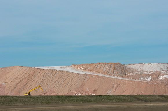 Hill of mined potash with a backhoe in front of it