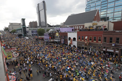 FILE - In this June 11, 2017, file photo, Nashville Predators fans fill the downtown streets outside Bridgestone Arena to watch Game 6 of the NHL hockey Stanley Cup Final between the Nashville Predators and the Pittsburgh Penguins, in Nashville, Tenn. The NFL draft is heading to Music City. League owners awarded the 2019 draft to Nashville during their annual spring meetings on Wednesday, May 23, 2018, in Atlanta. (AP Photo/Mark Humphrey, File)
