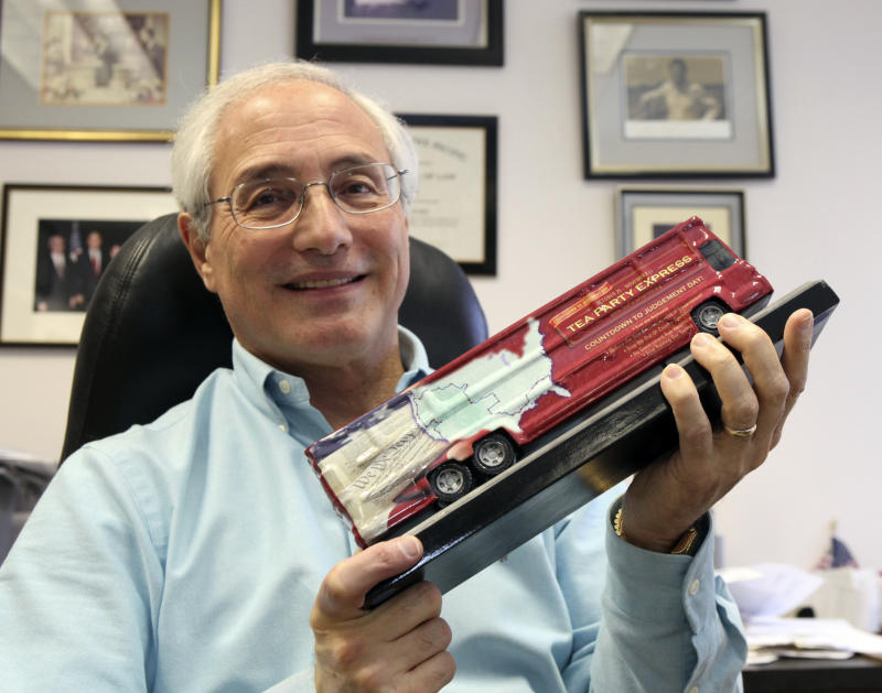 """FILE - In this March 23, 2010, file photo Sal Russo, the California-based co-founder of the Tea Party Express, holds a model of the Tea Party Express bus in his Sacramento, Calif., office.  The robust, hard-right political movement that helped drive the GOP's November triumphs still has clout, and perhaps a brilliant future. But in an January 2011 interview from Wyoming while visiting potential 2012 Senate candidates Russo said """"There's a little bit of expectation that they can do more than they really can do"""", and pointed out that Democrats still control the Senate and White House. (AP Photo/Rich Pedroncelli, File)"""