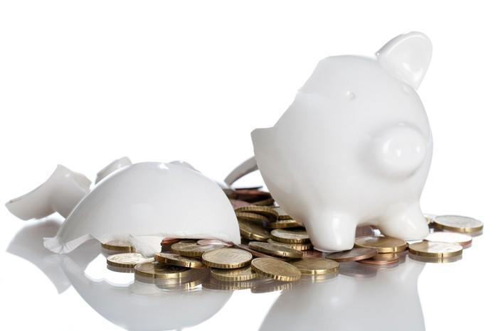 A broken white ceramic piggy bank with coins spilling out