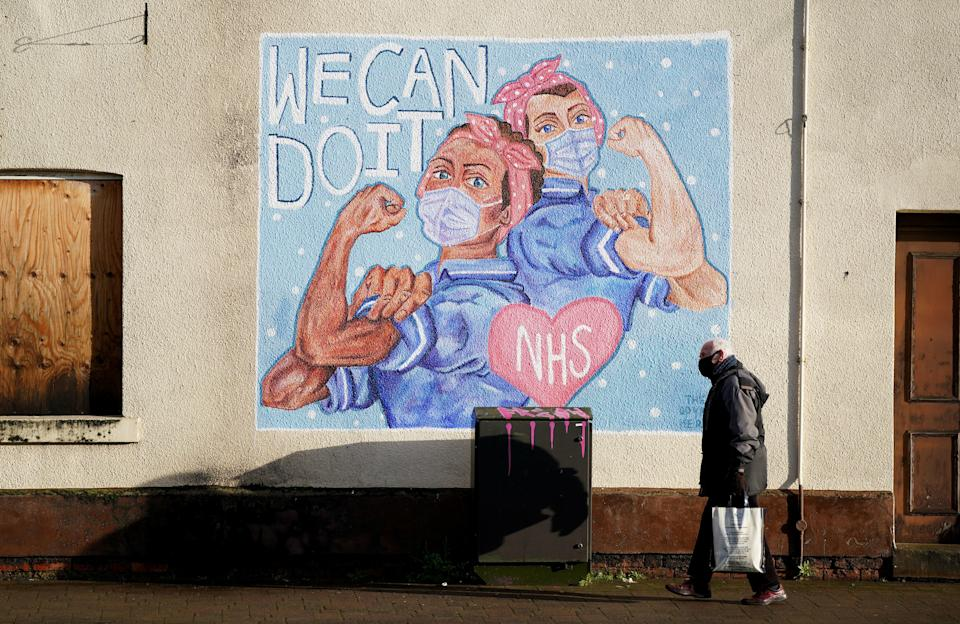 <p>A man walks past an NHS Mural in Loughborough, Leicestershire, during England's third national lockdown</p> (PA)