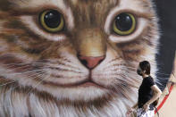 A woman wearing a face mask to help prevent the spread of the coronavirus walks past a painting of a cat in Quezon City, Philippines on Monday, May 24, 2021. The Philippines, a coronavirus hotspot in Southeast Asia, has received more than eight million doses of COVID-19 vaccine since February, but less than half have been administered so far, said officials, adding that among the problems were public hesitancy and low registration for the jabs. (AP Photo/Aaron Favila)