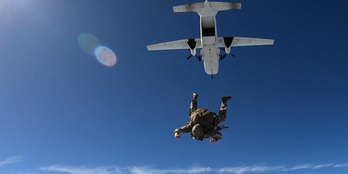 """A Special Operations Sniper exits a C-27 aircraft with his MK-22 Precision Sniper Rifle (PSR) in the """"side-mounted"""" configuration over Laurinburg drop zone, Laurinburg, North Carolina, during the PSR test"""