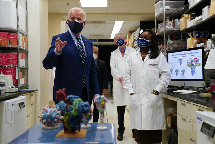 President Joe Biden speaks as Kizzmekia Corbett, an immunologist with the Vaccine Research Center at the National Institutes of Health looks on during a visit to the Viral Pathogenesis Laboratory at the NIH, Thursday, February 11, 2021, in Bethesda, Maryland. / Credit: Evan Vucci / AP