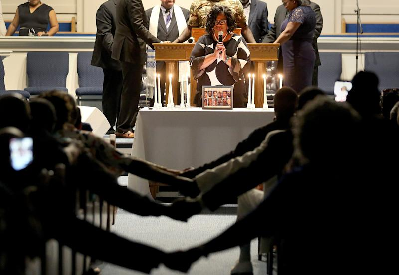 After lighting 12 candles, Veronica Coleman leads the congregation in prayer during a vigil for Ryan Keith Cox at the Piney Grove Baptist Church in Virginia Beach, Va., June 2, 2019. (Photo: Rob Ostermaier/AP)