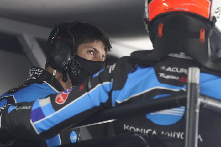 Ricky Taylor, left, talks with driving teammate Alexander Rossi in their pit stall during a practice session for the Rolex 24 hour race at Daytona International Speedway, Friday, Jan. 29, 2021, in Daytona Beach, Fla. (AP Photo/John Raoux)