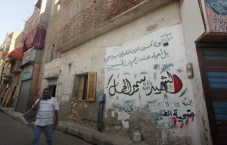 Ahmed El-Gamal, father of Samir, a 10-year-old Egyptian boy who died during clashes between supporters and opponents of deposed Islamist President Mohamed Mursi, walks in front house with graffiti in Suez