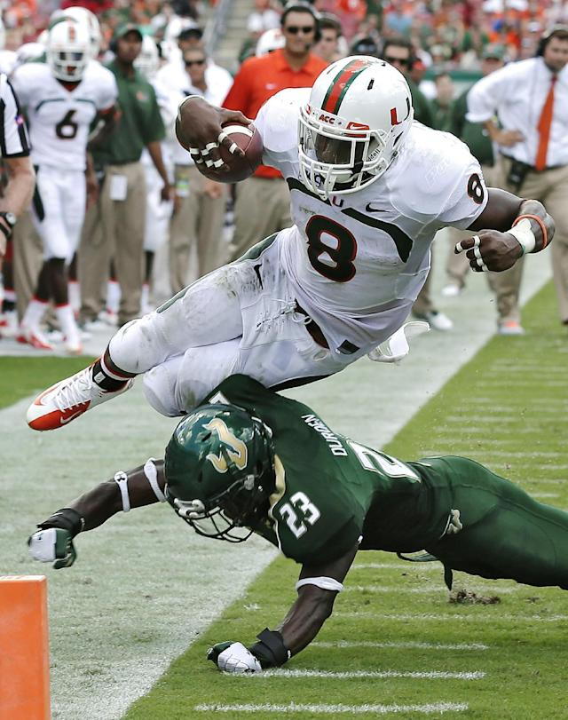 Miami running back Duke Johnson (8) is knocked out of bounds short of the goal line by South Florida defensive back Kenneth Durden (23) during the second quarter of an NCAA college football game Saturday, Sept. 28, 2013, in Tampa, Fla. (AP Photo/Chris O'Meara)