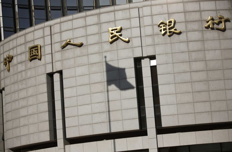 Fluttering Chinese national flag casts its shadow on the headquarters of the People's Bank of China, China's central bank, in central Beijing