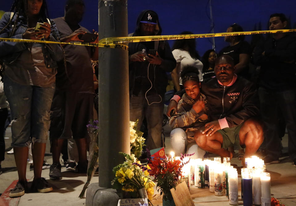 FILE - This March 31, 2019 file photo shows Haitian-French actor Jimmy Jean-Louis and his daughter Jasmin, 16, at a makeshift memorial for rapper Nipsey Hussle in Los Angeles. Hussle, 33, was shot and killed outside his Los Angeles clothing store in Los Angeles on March 31, 2019. A year after Hussle's death, his popularity and influence are as strong as ever. He won two posthumous Grammys in January, he remains a favorite of his hip-hop peers and his death has reshaped his hometown of Los Angeles in some unexpected ways. (AP Photo/Damian Dovarganes, File)