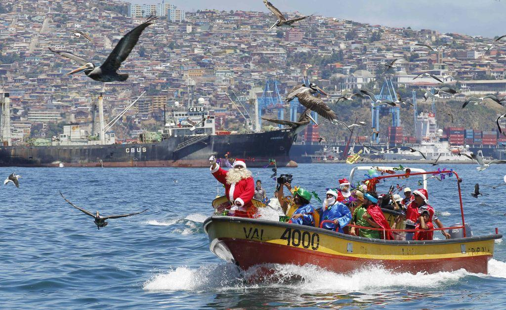 CHILE: Ruben Torres, dressed in a Santa Claus outfit, and fishermen wave to people from a boat on Christmas Eve along the coast of Valparaiso city, about 121 km (75 miles) northwest of Santiago. Every year, fishermen in Valparaiso organize a Santa Claus boat trip as people wait on the shore to receive their Christmas presents and well-wishes.