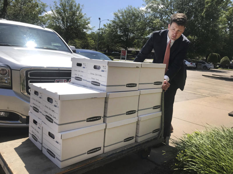 FILE - In this July 23, 2019, photo, Alex Gray, an attorney for Safe Surgery Arkansas, delivers petitions to the Arkansas secretary of state's office in favor of holding a referendum on a state law that expands the type of procedures optometrists can perform in Little Rock, Ark. Arkansas election officials on Friday, Aug. 2, 2019, rejected the attempt to hold a referendum next year on a new state law expanding what procedures optometrists can perform that has sparked an unusually expensive and public lobbying fight. (AP Photo/Andrew DeMillo, File)