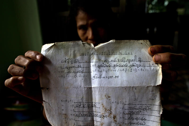 In this June 5, 2013 photo, a farmer displays a document proving her family's use of a paddy and payments made to the navy related to the land which was confiscated in 1992 by Myanmar security forces in Dala, Myanmar. Despite sweeping reforms since aquasi-civilian government was installed two years ago, authorities not only have broad powers to seize land in the name of national interest, but to arrest, try and imprison small-scale farmers and political activists who stand up in protest. (AP Photo/Gemunu Amarasinghe)