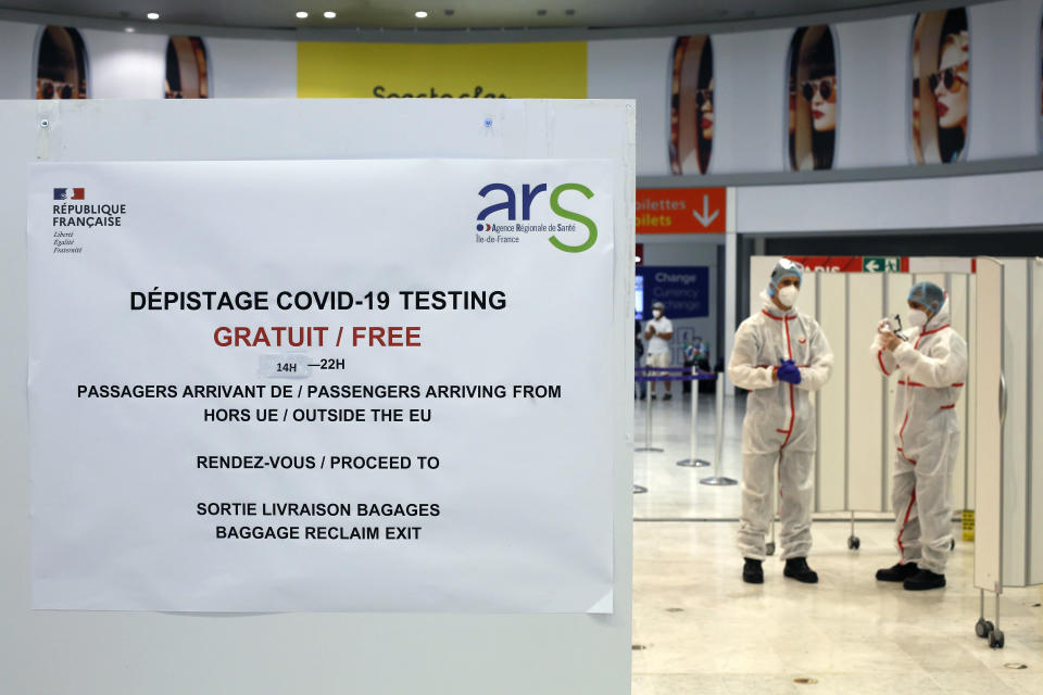 Health workers wait to test passengers with the COVID-19 test, at the Roissy Charles de Gaulle airport, outside Paris, Saturday, Aug. 1, 2020. Travelers entering France from 16 countries where the coronavirus is circulating widely are having to undergo virus tests upon arrival at French airports and ports.(AP Photo/Thibault Camus)