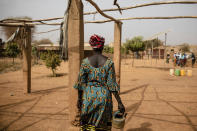 A displaced woman walks with a kettle Monday Feb. 8, 2021 in the Kaya camp, 100 kms North of Ouagadougou, Burkina Faso. A report by humanitarian groups says sexual assault cases in one region increased five-fold during a three-month period last year. Aid groups say jihadists are not the only perpetrators and that there has been a sharp increase in domestic violence and exploitation of displaced women by host communities. (AP Photo/Sophie Garcia)