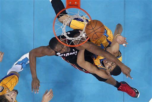 Miami Heat center Chris Bosh, top left, tries to block a shot by New Orleans Hornets forward Anthony Davis in the first half of an NBA basketball game in New Orleans, Friday, March 29, 2013. (AP Photo/Gerald Herbert)