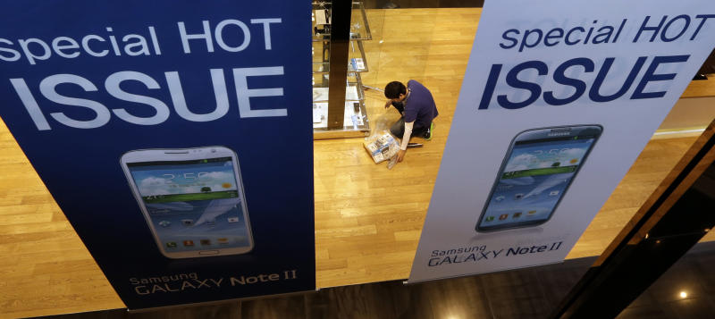 An employee of Samsung Eletronics Co. prepares to display Samsung products at a showroom of its headquarters in Seoul, South Korea, Friday, Oct. 26, 2012. Samsung's third-quarter net profit nearly doubled over a year earlier to a record high propelled by strong sales of Galaxy phones that helped widen its lead over rivals. (AP Photo/Lee Jin-man)