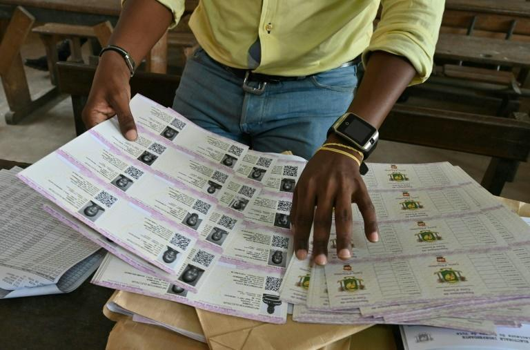 An Ivory Coast Electoral Commission official in Abidjan helps out with distribution of voting cards on October 14, 2020 ahead of the country's presidential election