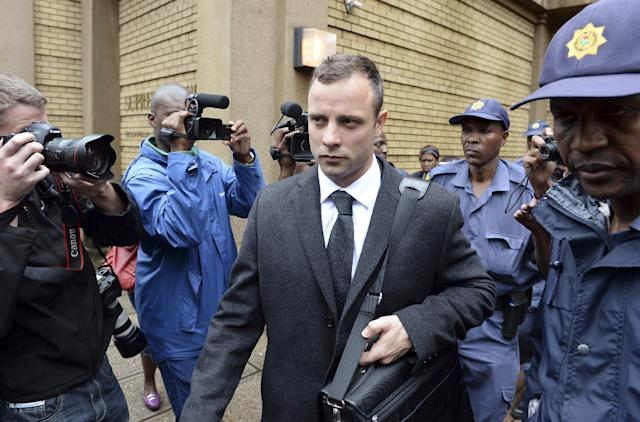 Oscar Pistorius is escorted outside court during a recess on the third day of his trial at the high court in Pretoria, South Africa, Wednesday, March 5, 2014, Pistorius is charged with murder for the shooting death of his girlfriend, Reeva Steenkamp, on Valentines Day in 2013. (AP Photo/Antoine de Ras) SOUTH AFRICA OUT
