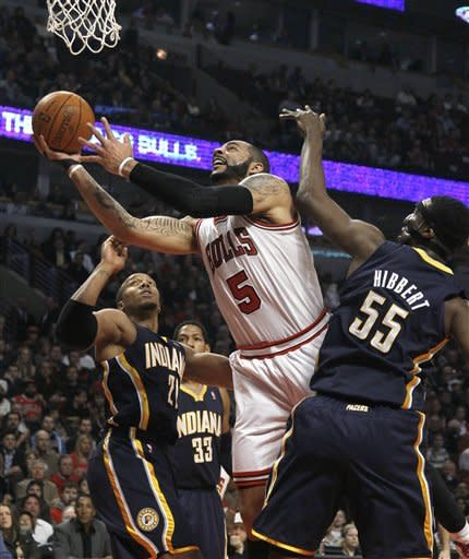 Chicago Bulls forward Carlos Boozer (5) scores past the defense of Indiana Pacers forward David West (21) and center Roy Hibbert (55), during the first half of an NBA basketball game on Wednesday, Jan. 25, 2012, in Chicago. (AP Photo/Charles Rex Arbogast)